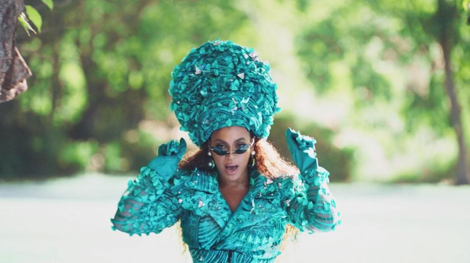 Beyoncé in Jerome LaMaar's hand-beaded Nigerian lace trench-jumper with built in gloves made of turquoise, jade, hematite, mother of pearl, silver, and Swarovski crystals.