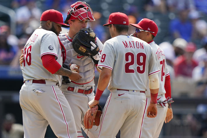 Philadelphia Phillies catcher J.T. Realmuto, second from left, talks to relief pitcher Jose Alvarado, left, as second baseman Nick Maton (29) and shortstop Ronald Torreyes (74) gather around for a mound conference of during the eighth inning of a baseball game against the New York Mets, Sunday, June 27, 2021, in New York. (AP Photo/Kathy Willens)
