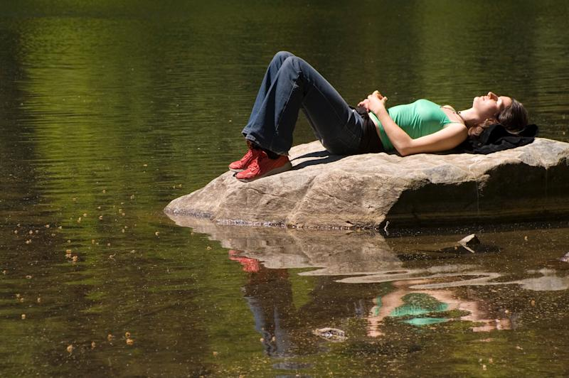 (GERMANY OUT) Junge Frau beim Sonnenbaden auf einem Felsen an einem See, woman lying on a rock at the lake (Photo by Wodicka/ullstein bild via Getty Images)