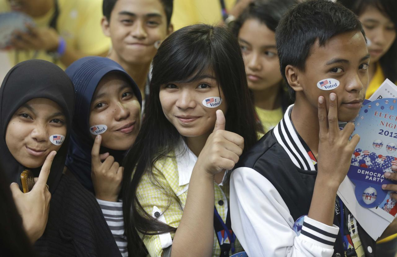 "Muslim students pose before a throng of photographers shortly after ""voting"" in the mock U.S. election at a shopping mall at suburban Quezon city, northeast of Manila, Philippines Wednesday, Nov. 7, 2012. Filipinos participated in a mock U.S. elections between President Barack Obama and Republican challenger Mitt Romney which was organized by the U.S. Embassy in Manila. (AP Photo/Bullit Marquez)"
