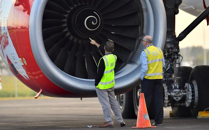 Officials inspect an engine of Malaysian budget carrier AirAsia X after it was diverted and forced to land because an engine was damaged during take-off - REUTERS