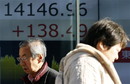Pedestrians walk past an electronic board showing Japan's Nikkei average outside a brokerage in Tokyo February 5, 2014. REUTERS/Yuya Shino