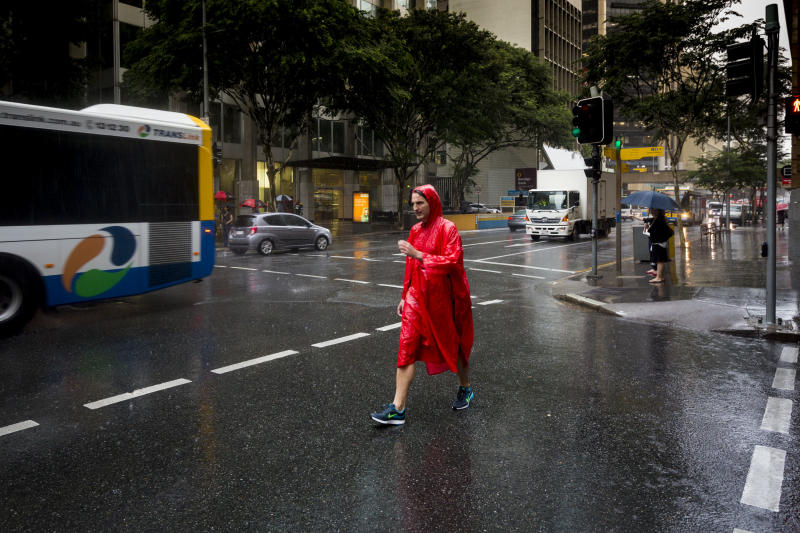 A stock image of rain falling in Brisbane's central business district as a man crossed a street in a poncho.