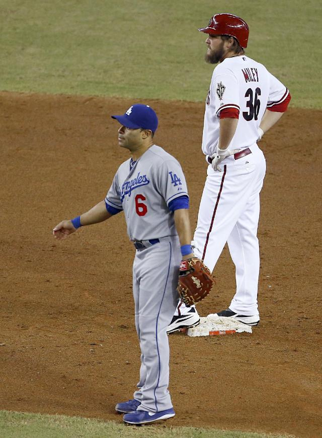 Arizona Diamondbacks' Wade Miley (36) stands on second base after hitting a two-run double as Los Angeles Dodgers' Jerry Hairston Jr. (6) waits for a throw in the third inning of a baseball game on Thursday, Sept. 19, 2013, in Phoenix. (AP Photo/Ross D. Franklin)
