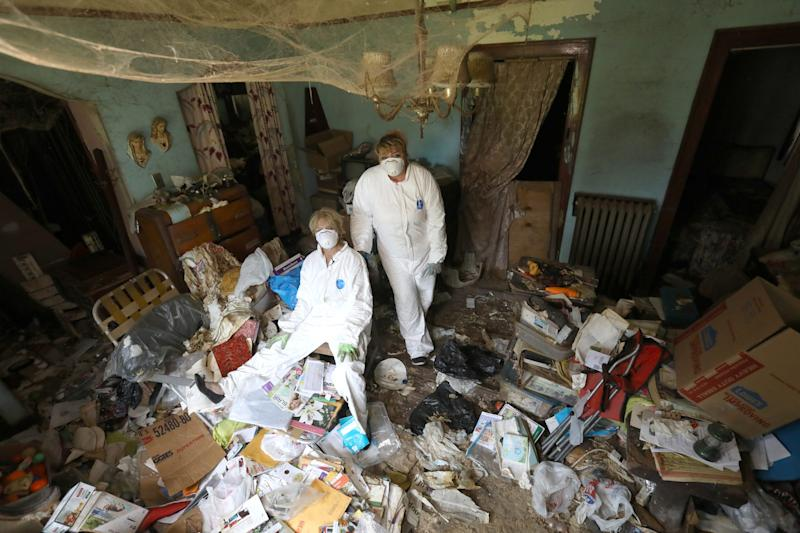 Linda Kajma (sitting) and friend and colleague Tamara Tracy inside the family room of Sally and Lorraine Honeycheck during a cleaning of the house on Sunday, June 23, 2019. The house was full of many items like old newspapers, torn mattresses covered in rat droppings, stacked up dishes and uneaten food is making it hard to Kajma to dig through and find valuable possessions, insurance forms, money and other important items left behind when Sally died.