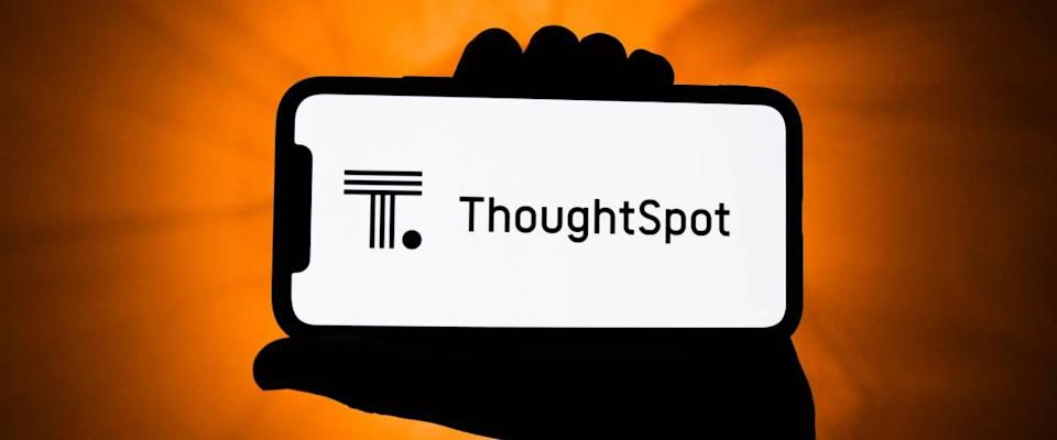 Hand holding up phone with ThoughtSpot logo on it.