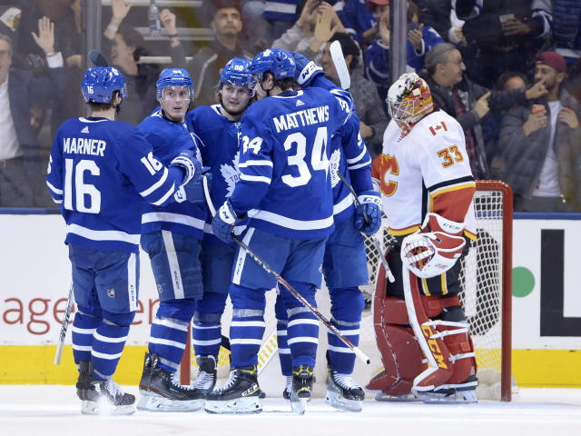 Toronto Maple Leafs right wing William Nylander (88) celebrates his goal with right wing Mitchell Marner (16), defenseman Tyson Barrie (94), center Auston Matthews (34) and center John Tavares, obscured, as Calgary Flames goaltender David Rittich (33) looks down during the third period of an NHL hockey game Thursday, Jan. 16, 2020, in Toronto. (Nathan Denette/The Canadian Press via AP)