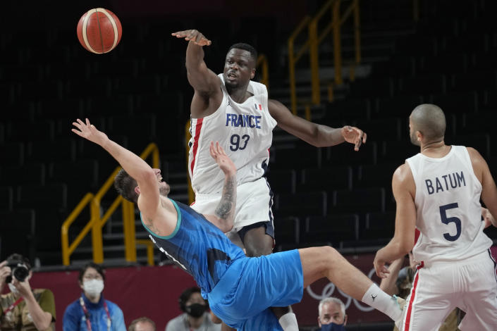France's Moustapha Fall (93) blocks Slovenia's Luka Doncic (77) during a men's basketball semifinal round game at the 2020 Summer Olympics, Thursday, Aug. 5, 2021, in Saitama, Japan. (AP Photo/Eric Gay)