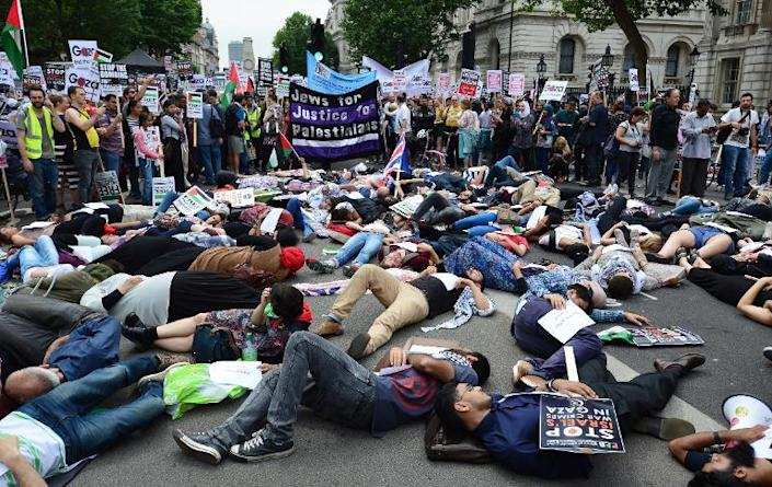 Protesters lie-down as they take part in demonstration against Israeli airstrikes in Gaza, during a rally in central London, on July 19, 2014 (AFP Photo/Carl Court)