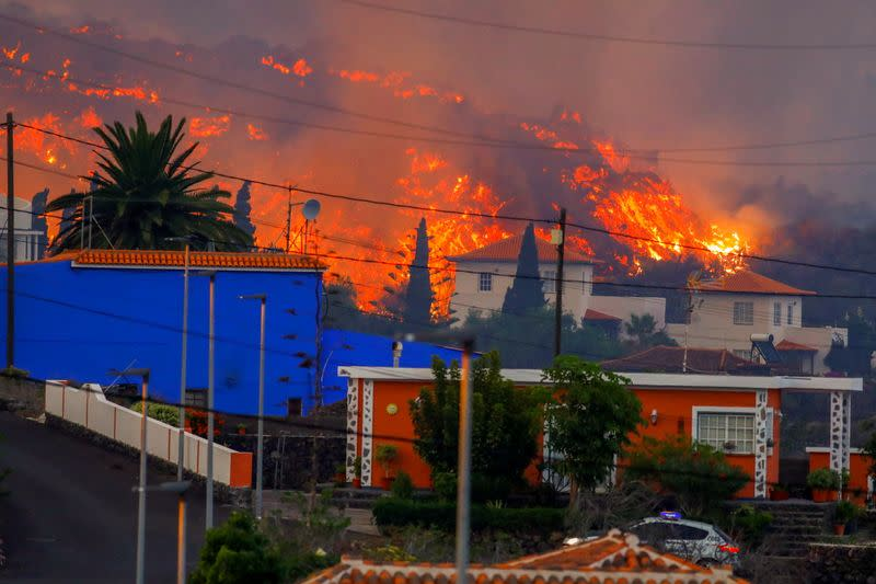Lava flows behind houses following the eruption of a volcano in Spain