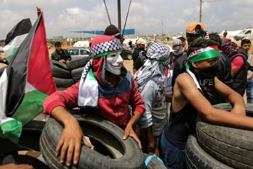 A Palestinian demonstrator wearing an Anonymous mask protests on the Israel-Gaza border during a fifth consecutive week of rallies dubbed the Great March of Return