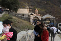 Armenians visit the 12th-13th century Orthodox Dadivank Monastery on the outskirts of Kalbajar, the separatist region of Nagorno-Karabakh, on Friday, Nov. 13, 2020. Under an agreement ending weeks of intense fighting over the Nagorno-Karabakh region, some Armenian-held territories, such as this area adjacent to the region, are passing to Azerbaijan. (AP Photo/Sergei Grits)