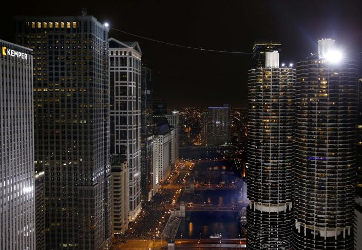 Daredevil Nik Wallenda walks along a tightrope between two skyscrapers suspended 500 feet (152.4 meters) above the Chicago River in Chicago, Illinois, November 2, 2014. (REUTERS/Jim Young)