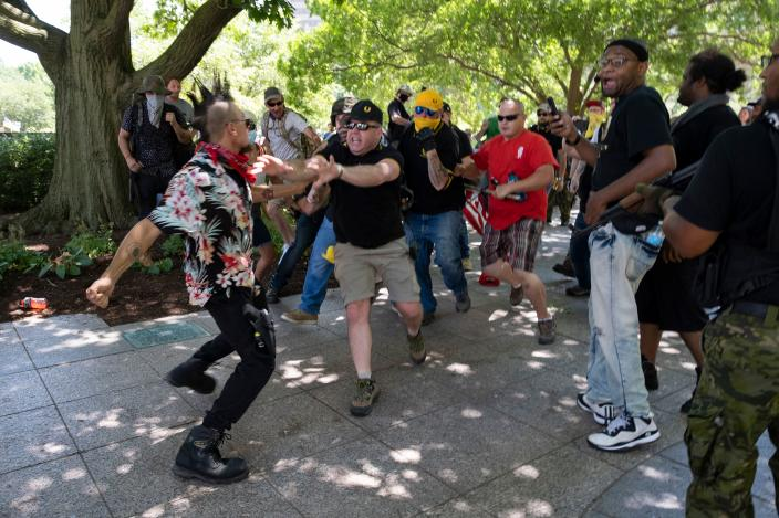 """A member of the """"boogaloo"""" movement, left, gets into a physical altercation with members of the Proud Boys during a right-wing protest in Columbus, Ohio, on July 18. (Jeff Dean/AFP via Getty Images)"""