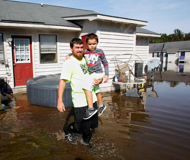 A man carries his son through flood waters surrounding their Greenville, North Carolina,home on Oct. 14, 2016, in the aftermath of Hurricane Matthew.