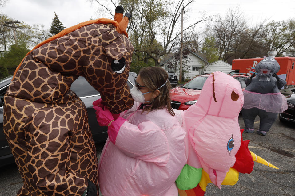 In this Monday, May 11, 2020 photo, Sarah Ignash helps a member of the T-Rex Walking Club with a giraffe costume in Ferndale, Mich. The group takes its unannounced strolls through neighborhoods on a quest to bring smiles to the faces of kids, and a few adults, while under Michigan's stay-at-home order because of the COVID-19 pandemic. (AP Photo/Carlos Osorio)