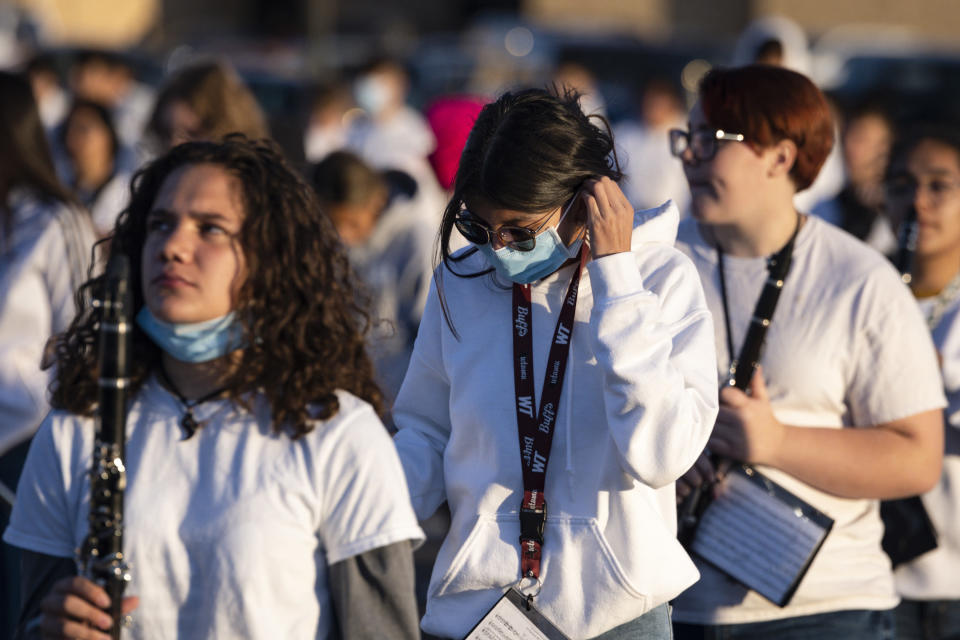 Marissa Equiniones, 17, center, puts on her face mask between drills during marching band practice Thursday, Sept. 23, 2021 in Odessa, Texas. (Eli Hartman/Odessa American via AP)