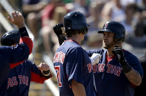 Boston Red Sox's Mike Napoli, right, is high-fived by teammates after hitting a 3-run home run in the fourth inning of a spring training exhibition baseball game against the Minnesota Twins, Thursday, March 7, 2013, in Fort Myers, Fla. (AP Photo/David Goldman)