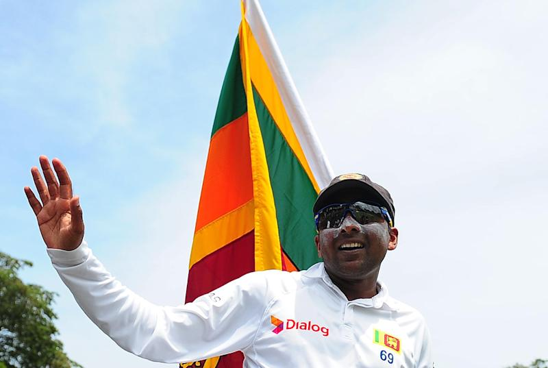 Sri Lankan cricketer Mahela Jayawardene waves to the crowd as his teammates carry him around the pitch in a lap of honour in Colombo on August 18, 2014