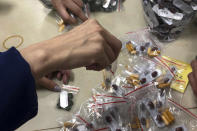 FILE - In this Sunday, Dec. 1, 2019, photo, workers pack multi-colored supplement pills in small resealable bags at an industrial building in Hong Kong. By day, the small commercial kitchen in a Hong Kong industrial building produces snacks. At night, it turns into a secret laboratory assembling a detox kit to help frontline pro-democracy protesters counter ill-effects from repeated exposure to tear gas. (AP Photo)