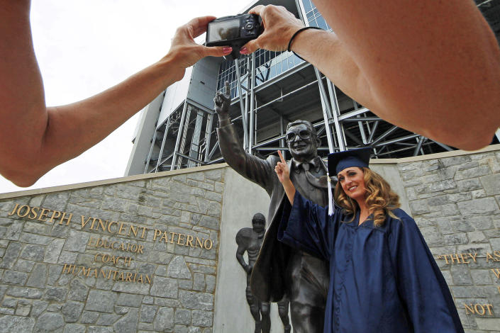 Gina DiJohnson, who will graduate from Penn State University in three weeks, poses for a picture with a statue of former Penn State Football coach Joe Paterno outside Beaver Stadium on the Penn State campus Wednesday, July 11, 2012. The Freeh Report on the Jerry Sandusky child sex scandal at Penn State will be released Thursday morning. (AP Photo/Gene J. Puskar)