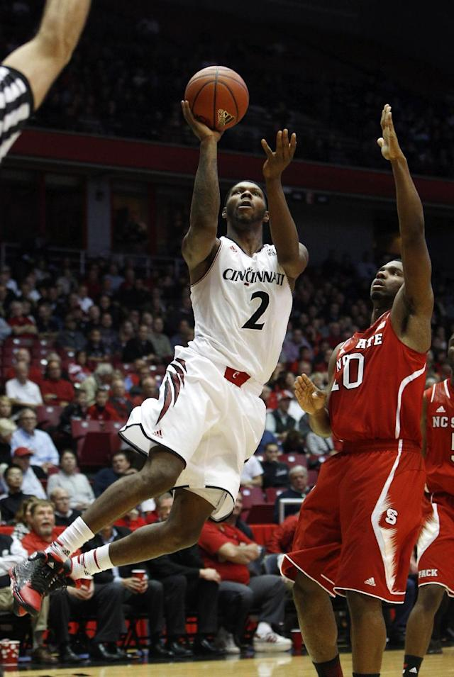 Cincinnati forward Titus Rubles (2) goes up for a shot against North Carolina State guard Patrick Wallace during the first half of an NCAA college basketball game Tuesday, Nov. 12, 2013, in Cincinnati. (AP Photo/David Kohl)