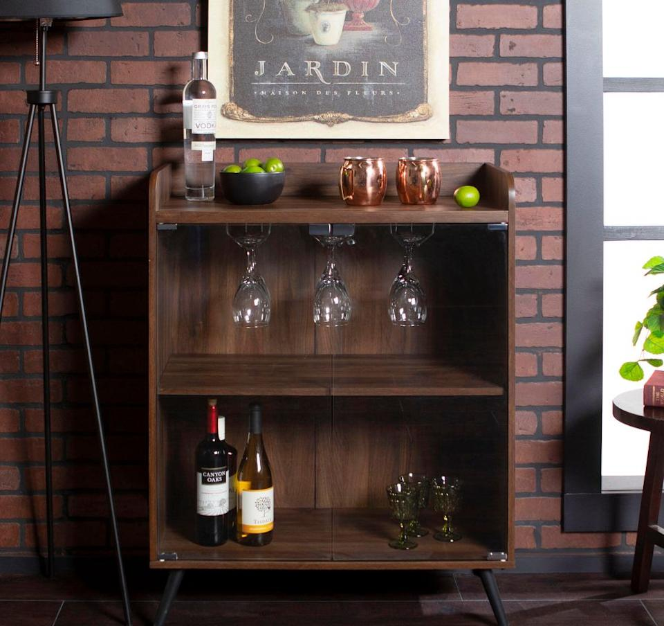 """This cabinet includes astemware rack to store glassware, atop shelf for limes and ice, and two shelves underneath for bottles. The dark wood will definitely fit right in with the rest of your living room. <a href=""""https://fave.co/31Syont"""" target=""""_blank"""" rel=""""noopener noreferrer"""">Originally $241, get it now for $142 at The Home Depot</a>."""