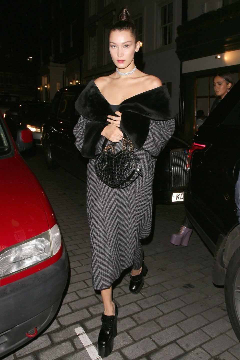 <p>Bella Hadid in platforms and a fur lined wrap dress at Lou Lou's for the Love Magazine party on Day 4 of London Fashion Week Spring/Summer 2017.</p>
