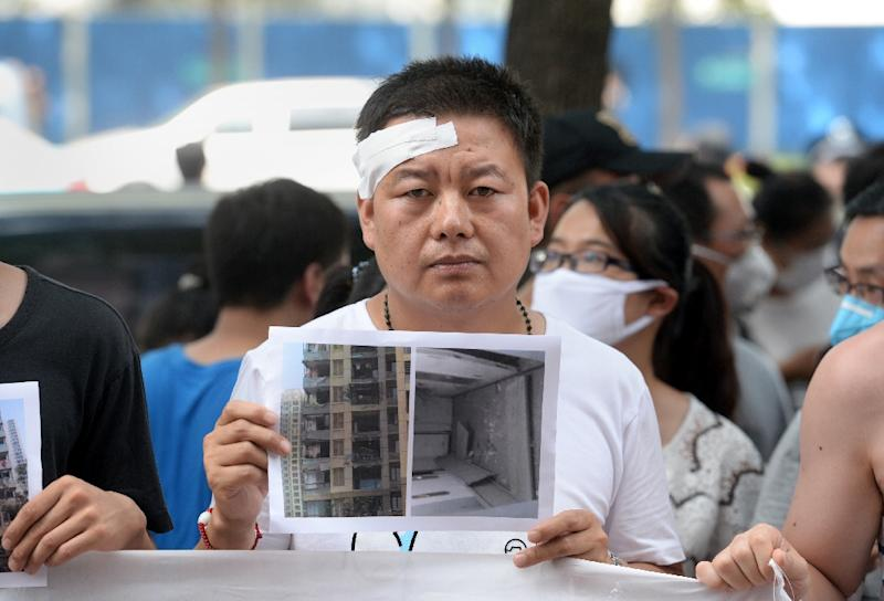 A man who was injured in the blasts holds a photo of his damaged home, as he joins people protesting in Tianjin on August 16, 2015 (AFP Photo/)
