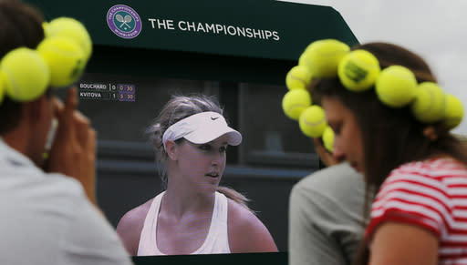 Spectators watch Eugenie Bouchard of Canada on a large video screen as she is defeated by Petra Kvitova of Czech Republic in the women's singles final against Eugenie Bouchard of Canada at the All England Lawn Tennis Championships in Wimbledon, London Saturday, July 5, 2014. (AP Photo/Ben Curtis)