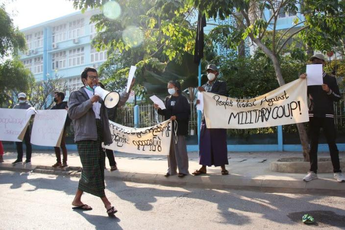 People protest on the street against the military after Monday's coup, outside the Mandalay Medical University in Mandalay