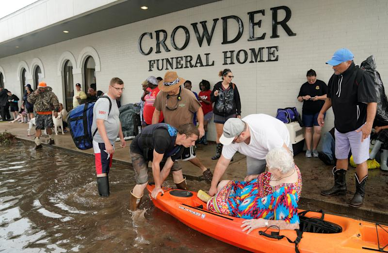 People wait to be evacuated from flood waters from Hurricane Harvey in Dickinson, Texas on Aug. 27, 2017.