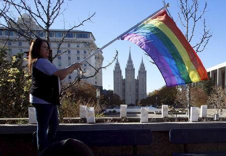 Sandy Newcomb stands with a flag near the Salt Lake Temple after members of The Church of Jesus Christ of Latter-day Saints mailed their membership resignation to the church in Salt Lake City, Utah November 14, 2015. REUTERS/Jim Urquhart