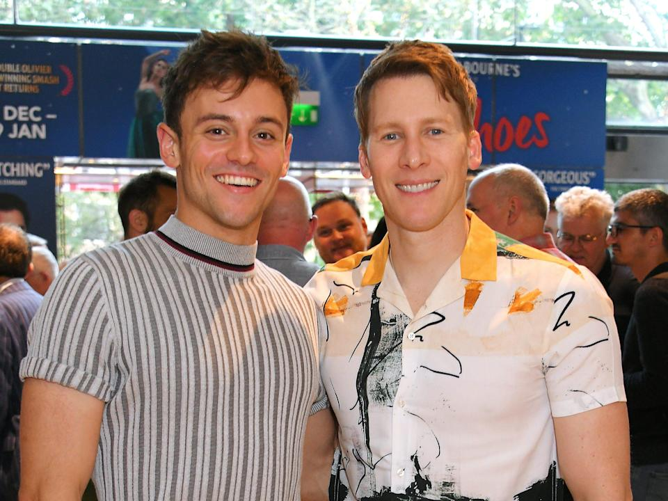 Tom Daley and Dustin Lance Black in 2019 smiling at camera with crowd behind them