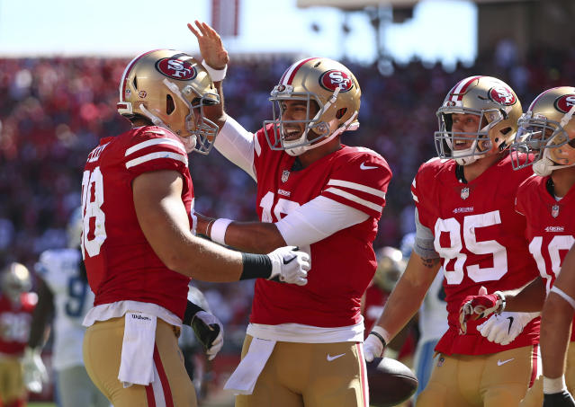 San Francisco 49ers tight end Garrett Celek, left, is greeted by quarterback Jimmy Garoppolo, center, after scoring a touchdown during the second half of an NFL football game against the Detroit Lions in Santa Clara, Calif., Sunday, Sept. 16, 2018. At right is San Francisco 49ers tight end George Kittle (85).(AP Photo/Ben Margot)