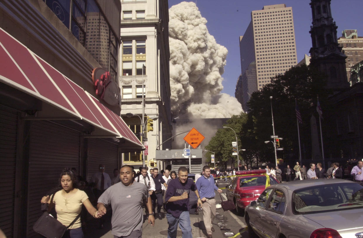 People run from the collapse of the north tower of the World Trade Center in New York, Sept. 11, 2001. (Suzanne Plunkett/AP)