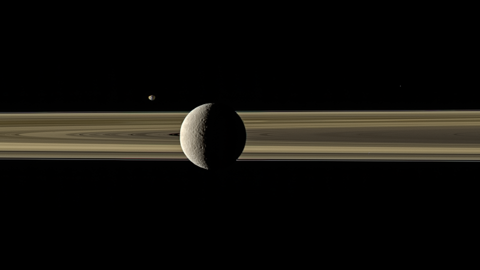 Saturn's moons Rhea and Janus tango on opposite sides of the planet's famous ring system in this new color-enhanced image from NASA's Cassini orbiter. Rhea, Saturn's second-largest moon, is visible in the foreground, while the smaller moon Janus is pictured in the distance across the rings. Citizen scientist Kevin Gill recently processed this 10-year-old view of Saturn and two of its moons using calibrated red, green and blue filtered images captured by the Cassini spacecraft on March 28, 2010.