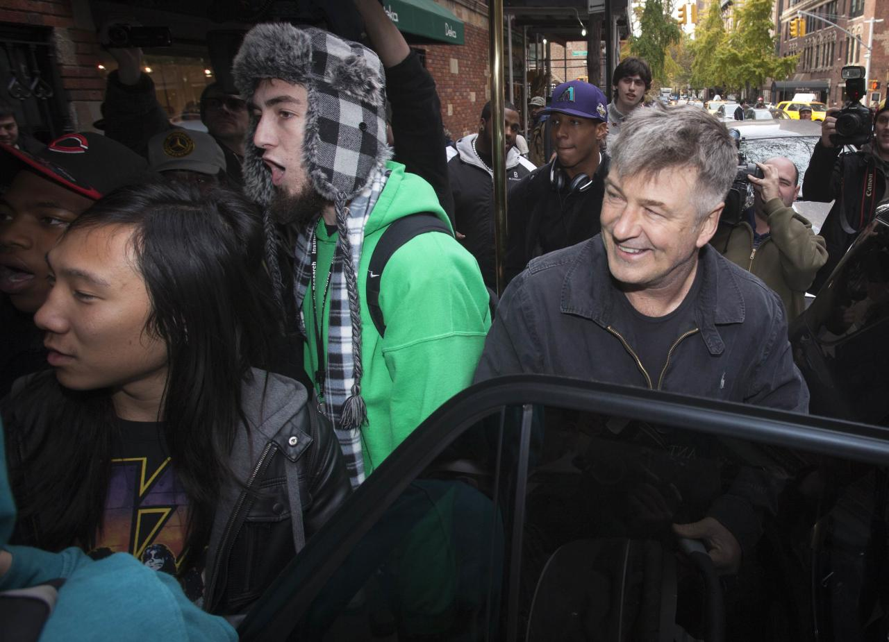 Actor Alec Baldwin laughs during a verbal altercation between people he had asked to block the media from taking photos and photographers, outside of his apartment in New York November 15, 2013. Baldwin asked the group of men to help him block the media from getting photos of him and his wife. Baldwin assaulted a reporter earlier in the day, according to local media. In the earlier incident, he smacked a mobile phone from the reporter's hands and shoved him against a car. REUTERS/Carlo Allegri (UNITED STATES - Tags: MEDIA ENTERTAINMENT)