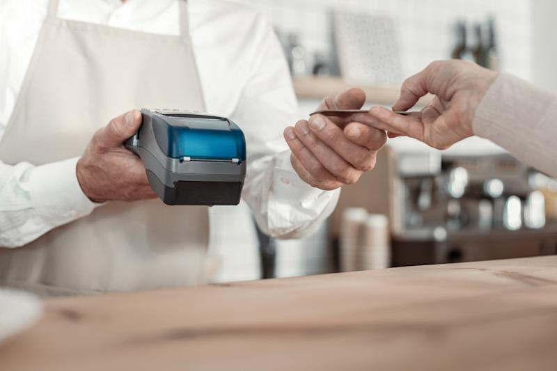 A hand hands a credit card to a cafe barista holding an electric point-of-sale device in his hand.