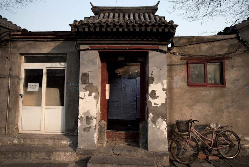 In this photo taken on Dec. 26, 2012, a bicycle is parked outside a Hutong home with a demolition notice seen behind the entrance wall near the historical Drum and Bell Tower in Beijing. The district government wants to demolish these dwellings, move their occupants to bigger apartments farther from the city center and redevelop a square in 18th century Qing Dynasty fashion. (AP Photo/Andy Wong)