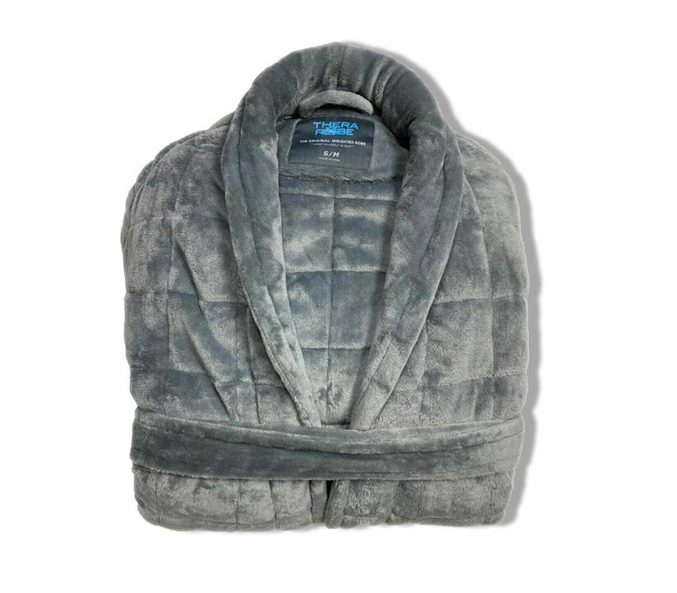 """<p>Weighted blankets are <em>so</em> 2020. Meet the <a href=""""https://therarobe.com/product/thera-robe/"""" rel=""""nofollow noopener"""" target=""""_blank"""" data-ylk=""""slk:Therarobe"""" class=""""link rapid-noclick-resp"""">Therarobe</a>, which has all the soothing, anxiety-reducing benefits of a weighted blanket but comes with an added bonus: It feels like a big, warm hug, and who doesn't want to gift one of those?</p> <p><strong>$200, <a href=""""https://therarobe.com/product/thera-robe/"""" rel=""""nofollow noopener"""" target=""""_blank"""" data-ylk=""""slk:therarobe.com"""" class=""""link rapid-noclick-resp"""">therarobe.com</a></strong></p> <p>*<strong>Use discount code EWGIFT10 for 10% off</strong></p>"""
