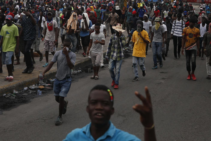 Protestors calling for the resignation of Haitian President Jovenel Moise march toward the National Palace before being stopped by police in Port-au-Prince, Haiti, Tuesday, Oct. 1, 2019. While there were sporadic demonstrations on Tuesday, another protest scheduled for Wednesday threatened to once again paralyze Haiti's capital and nearby communities, which have endured violent demonstrations for nearly a month as anger grows over corruption, spiraling inflation and dwindling supplies of food and gasoline. (AP Photo/Rebecca Blackwell)