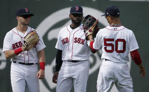 Boston Red Sox outfielders, from left to right, Andrew Benintendi, Jackie Bradley Jr. and Mookie Betts celebrate after defeating the Baltimore Orioles in a baseball game in Boston, Sunday, May 20, 2018. (AP Photo/Michael Dwyer)
