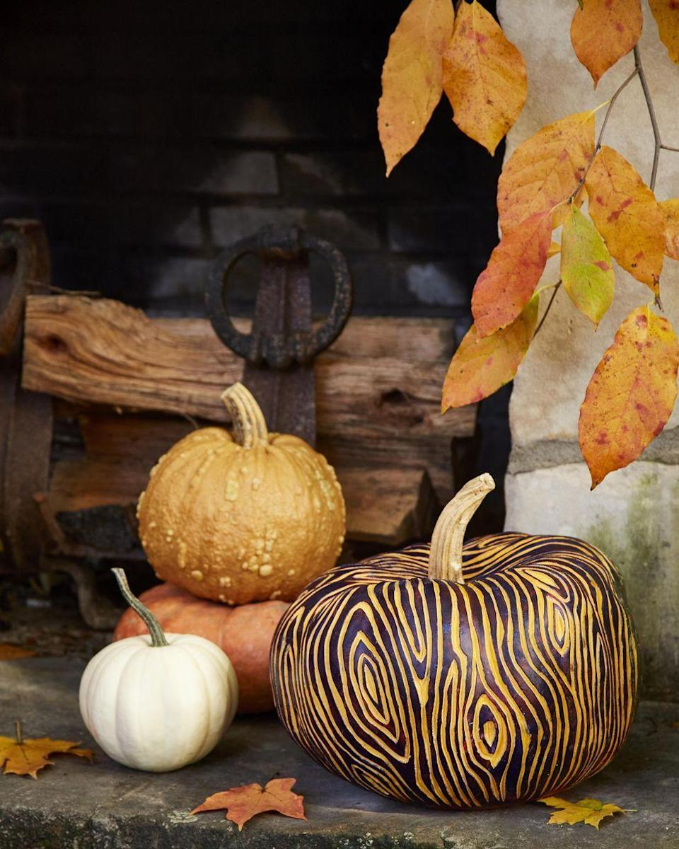 <p>For a totally rustic look, imitate the look of wood grains by lightly sketch a faux bois pattern on a pumpkin with a pencil. Then, use a linoleum carving tool to etch out the pattern. Once complete, paint unetched part of the pumpkin with acrylic paint. </p>