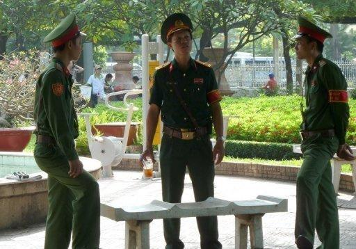 """Vietnamese soldiers at a public park near the Ho Chi Minh City People's Court. A court in southern Vietnam has jailed three bloggers for """"anti-state propaganda"""", including one whose case has been raised by US President Barack Obama, at a brief but dramatic hearing"""