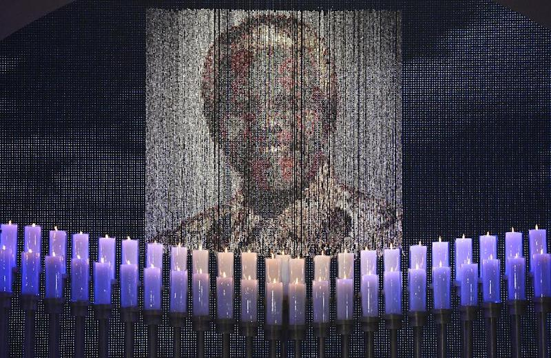 Candles illuminate a portrait of Nelson Mandela during the funeral service for former South African president Nelson Mandela in Qunu, South Africa, Sunday, December 15, 2013. (AP Photo/Odd Andersen, Pool)