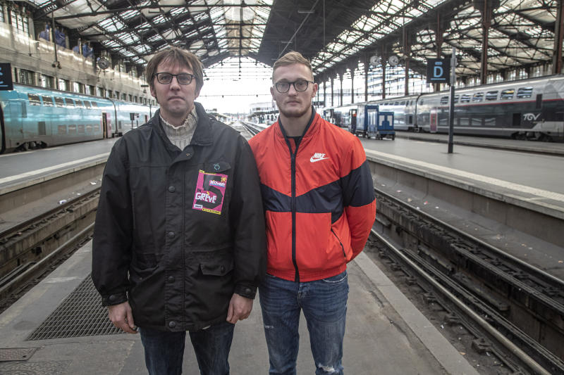 In this photo taken Saturday Nov. 30, 2019, Gilles Pierre, left, a metro driver for the Paris public transport company RATP, and Vincent Le Faucheur, 23, a train traffic controller for the national railway company SNCF pose at the Gare de Lyon train station in Paris. France is getting ready for massive, nationwide transport strikes Thursday, disrupting trains, buses and airlines, protesting against government plans to overhaul the state pension system.  (AP Photo/Michel Euler)