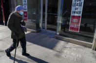 A pedestrian walks past a vacant commercial property and graffiti calling on President Trump to be removed from office and arrested, Sunday, Jan. 10, 2021, in the Hell's Kitchen neighborhood of New York. The boarded-up windows and For Rent signs are all over the place in Manhattan's Hell's Kitchen neighborhood. Nearby, the Broadway theaters are all dark. But the economic darkness brought on by the coronavirus pandemic has had a few bright spots. A couple of well-loved venues have gotten financial boosts, thanks to online fundraising campaigns and even a telethon. (AP Photo/Mary Altaffer)