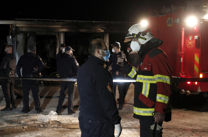 Firemen talk to each other standing near the burned out makeshift hospital in North Macedonia's western city of Tetovo, early Thursday, Sept. 9, 2021. Police and public health officials in North Macedonia say at least 10 people have died and many others have been injured by a fire at the makeshift hospital for COVID-19 patients. (AP Photo/Boris Grdanoski)