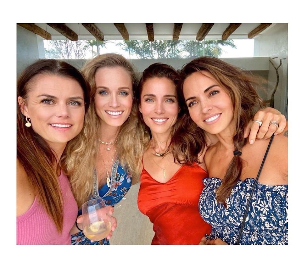 Elsa Pataky in a red top and brunette hair posing with friends